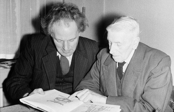 Frans Mars en Pieter Boorsma kijken in het boek Duizend Zaanse Molens