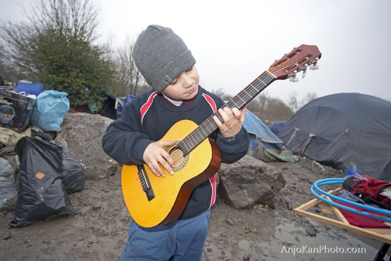 foto-2-duinkerken-24-01-2016-een-groep-vrijwilligers-brengen-muziek-instrumenten-en-hoepels-naar-het-kamp-een-jongetje-verdwijnt-in-de-muziek-tussen-het-vuilnis-in-de-modder-speelt-hij-op-zijn-g