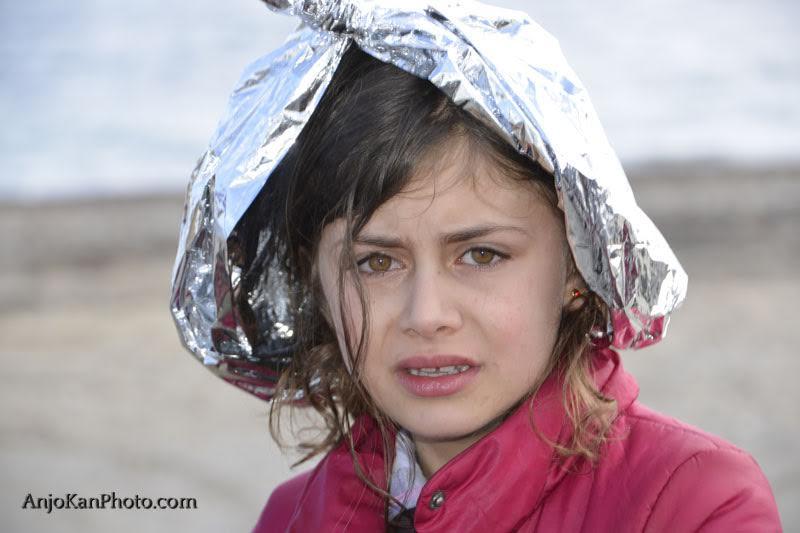 foto-4-een-syrisch-meisje-net-gearriveerd-op-lesbos-de-emergency-blanket-tegen-de-kou-is-door-vrijwilligers-omgetoverd-tot-een-hoofddeksel